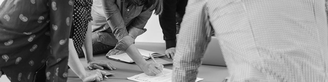 A group of people work around a shared printed document in a casual business setting.
